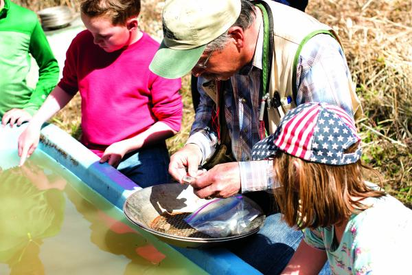 Forth graders from Cardwell and Twin Bridges Schools at the annual Bear Creek Days huddle around Kevin Suzuki and a tub of water, as he shows them how to pan for gold and other rocks Tuesday, May 14. (H. Kearse)