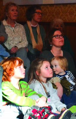 Teresa Aldrich of Montana Raptor Conservation Center held the rapt attention of these young visitors to the Elling House when she explained the distinguishing features of raptors: their talons, beaks and eyes. (R. Colyer photos)