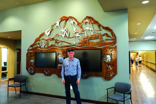 Artist Del Bieroth with the sculpture he created for the interactive donor wall in the entryway of the new Ruby Valley Medical Center. (Photo courtesy of Debra McNeill)