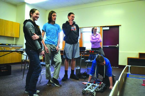 Trista Redfield, C. J. Wayland, and Matthew Kaiser and coach Jennifer Elser look over Ethan Wayland's work with robotics in the competition space