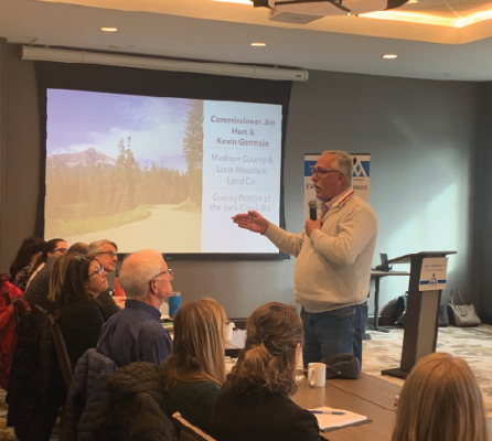 Commissioner Jim Hart picked-up the microphone and approached the crowd to discuss the complexities of the Jack Creek Road issue at the Nov. 6 Madison and Gallatin Counties Joint Commission meeting . PHOTO BY JANA BOUNDS