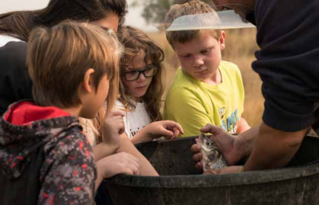 Montana Fish, Wildlife and Parks Conservation Technician Lucas Bateman shows Twin Bridges' students a whitefish during Kids' River Resource Day at the Hamilton Ranch in Twin Bridges Sept. 17. PHOTO BY HANNAH KEARSE