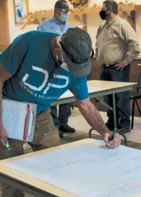 Brad Schwend votes for the town to focus on economic development during the growth policy and capital improvement plan public meeting at the Sheridan Senior Center Oct. 12. PHOTO BY HANNAH KEARSE
