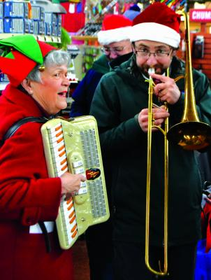 Led by Ennis music director Andrew Scruggs (right) carolers traversed up and down Main Street and even entered businesses like Shedhorn Sports to spread some holiday cheer.
