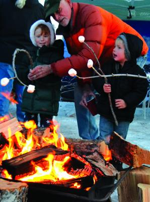 A S'mores station — complete with fires for keeping warm and roasting marshmallows — proved to be one of the more popular additions to the Ennis Christmas Stroll on Friday, December 7.