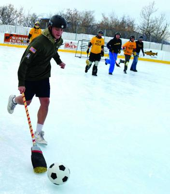 """A member of the """"Ruby Valley Beer Removal"""" broomball team runs—and slides—for the goal on Saturday, January 5 at Virginia City's Winter Fest. While the slide would be spectacular, the goal would unfortunately be a miss."""