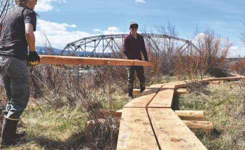 Madison River Foundation team members transport planks to construct a trail near Three Dollar Bridge