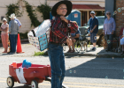 A Pony Day parade winner walks down Broadway Street and tosses candy to spectators as bubbles float around his Candy Wagon. PHOTO BY HANNAH KEARSE