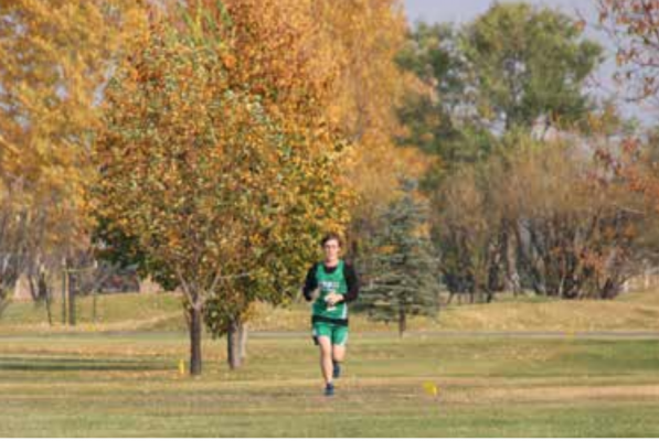 Kyle LaClair running during the Rusty Raisland Invite with beautiful fall colors behind him. PHOTO BY KATHY LACLAIR
