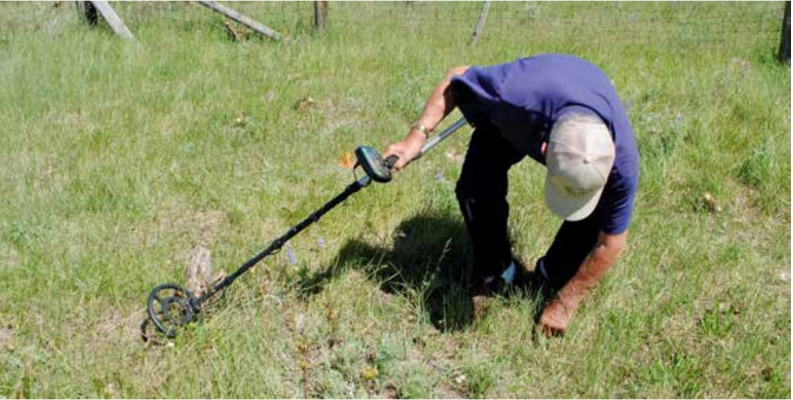 Bill Tate uses his metal detector to find the metal stakes inside the fenced-in area where it is possible that Virginia City volunteers are buried. PHOTO BY KEELY LARSON