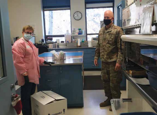 The lab workers have been so grateful to the National Guard members and the environmental laboratory team that have helped them through the testing increases. On the left, Kathy Manion, in charge of the accessioning, and Todd Monroe with the National Guard on the right. PHOTO COURTESY OF DEBORAH GIBSON