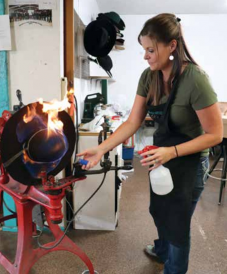 Ericka Kirkpatrick demonstrates the hat smoothing process. After sanding the felt a torch is used to get rid of any remaining fibers, creating a hat as smooth as velvet. PHOTO BY JOLENE PALMER