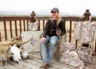 Kelsey Hubner at her Jeffers home with a set of Classic Equine travel bags featuring her artwork. To Hubner's right are cattle skulls being prepared for painting. In her left hand, Hubner holds a branding iron with her registered K-Bar-Heart brand, often seen in her artwork.