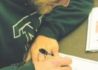 Nate Konen, Twin Bridges senior, signs dozens of autographs for his fellow Falcons Dec. 18. PHOTO BY HANNAH KEARSE